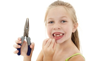 Pretty Young Girl Child Pulling Loose Tooth with Pliers