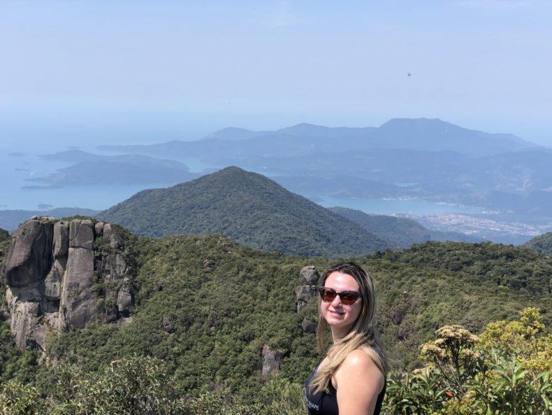 Feliz da vida no alto da montanha com a cidade de Paraty ao fundo