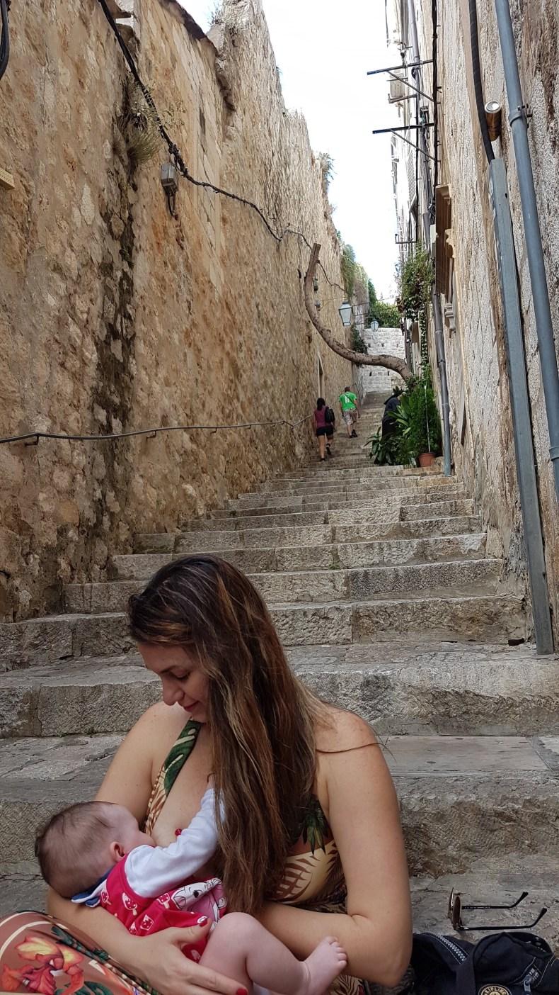 Viajar com bebês: alimentação e roteiro. Pausa para o lanchinho sentada nas escadarias históricas de Dubrovnik, Croácia. Amamentação exclusiva.