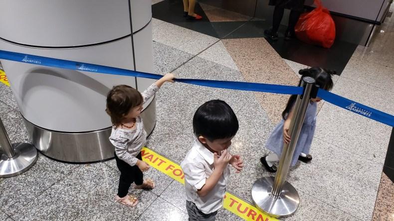 Crianças na fila de Imigração do Aeroporto internacional da Malásia