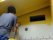 "A last-minute design switch, bringing the ""cap"" of yellow onto the walls so we don't have to tile alllll the way up. In this pic, Fitz is sanding off a pen mark he drew that would NOT disappear! Magic pen!"