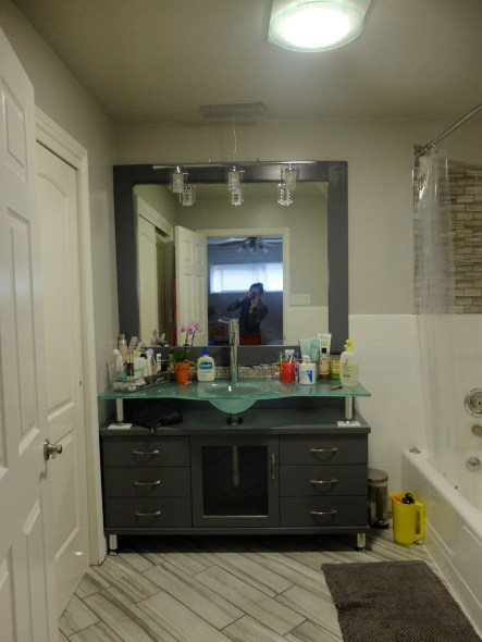 New vanity with frosted glass countertop and built-in sink.