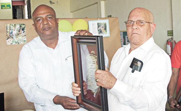 Lic. Juan Silvestre de Jesús entrega reconocimiento al profesor y productor Rafael Valerio Reyes (derecha).