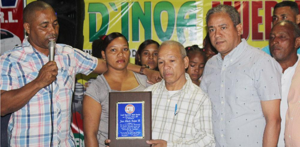 El alcalde municipal Cesar Castro entrega una placa de reconocimiento a los familiares de Juan Alberto Ramos.