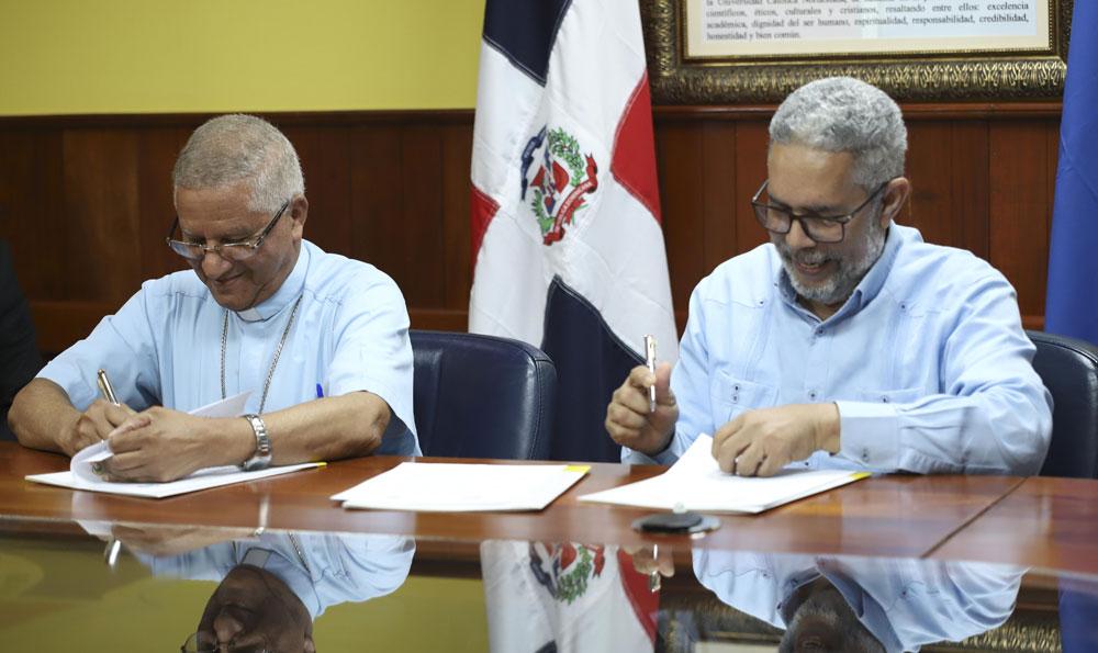 Monseñor doctor Fausto Ramón Mejía Vallejo, Gran Canciller y Rector de la UCNE y el licenciado José Wenceslao Ceballos Fernández, Director Ejecutivo de Centro Casas Comunitarias de Justicia firman el convenio.