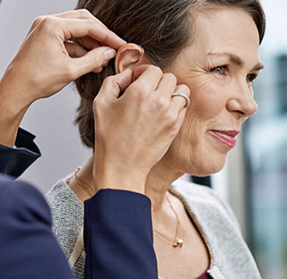 person putting a hearing aid in a lady's ear