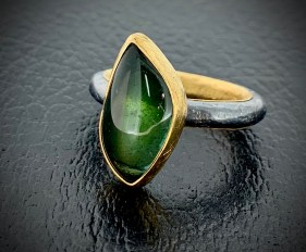 Blue-green Afghan tourmaline (looks more green in photo), 22k gold inner band and setting, oxidized sterling. Size 7.