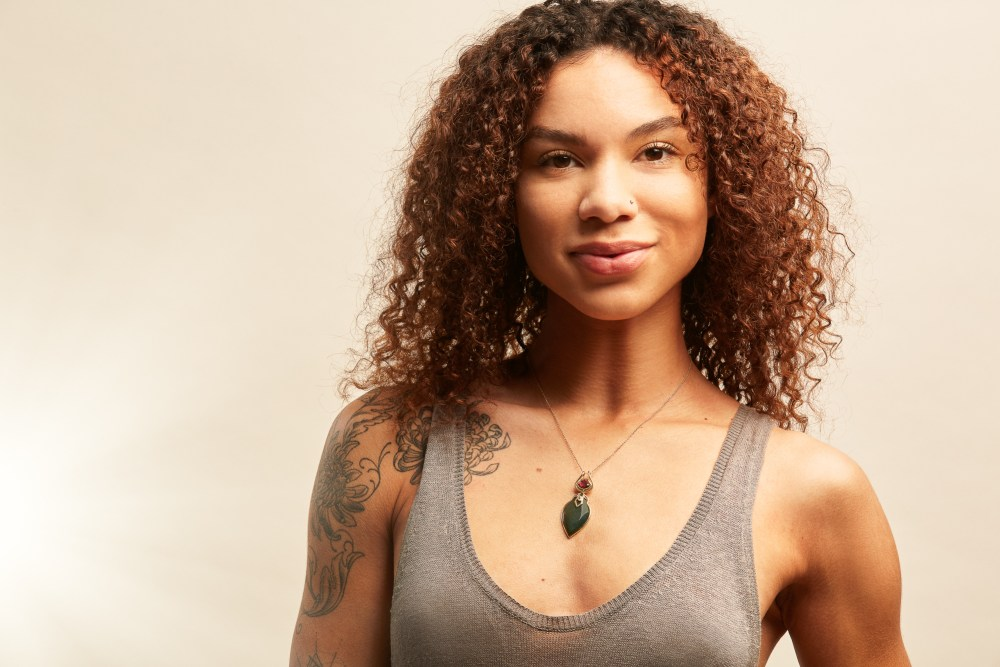 jewelry advertising image showing black model wearing green necklace