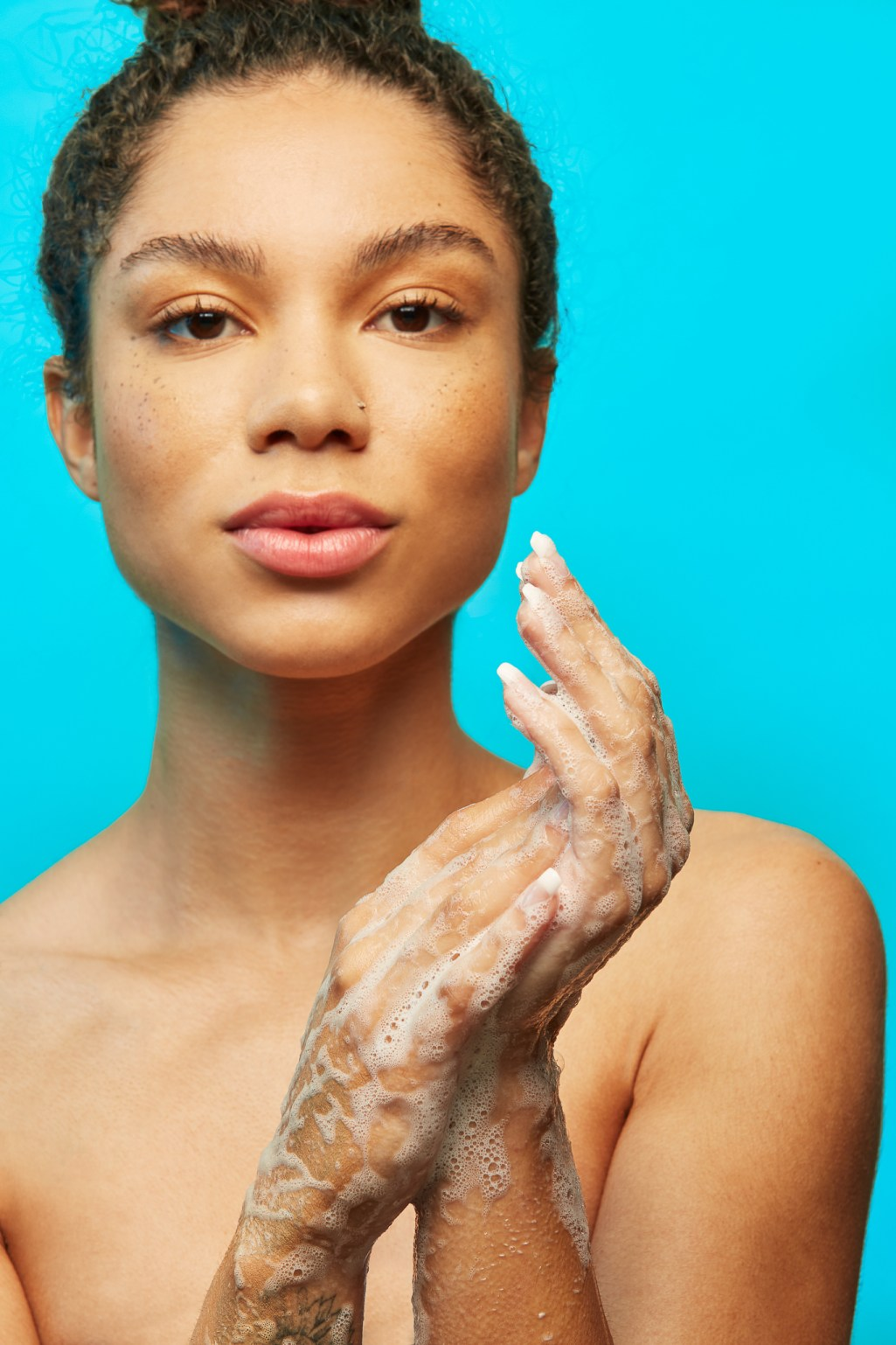 Advertising image, beauty portraits of black model with freckles and soapy hands. Photographer Ella Sophie, San Francisco California