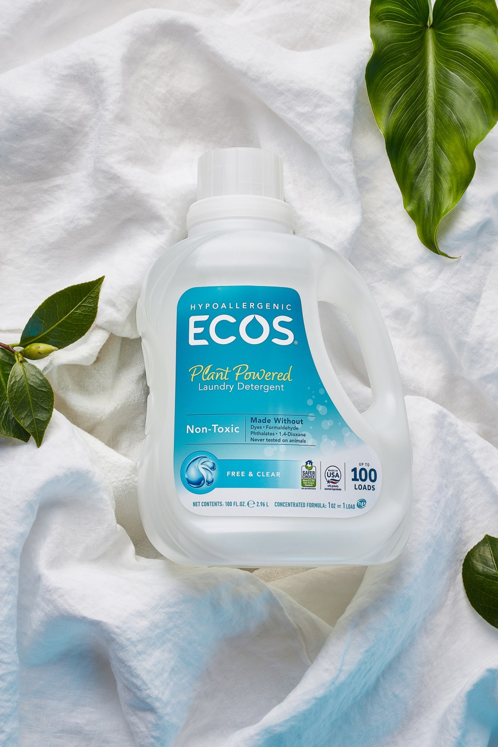 Still life of ECOS laundry detergent with white linen and green leaves by Photographer Ella Sophie