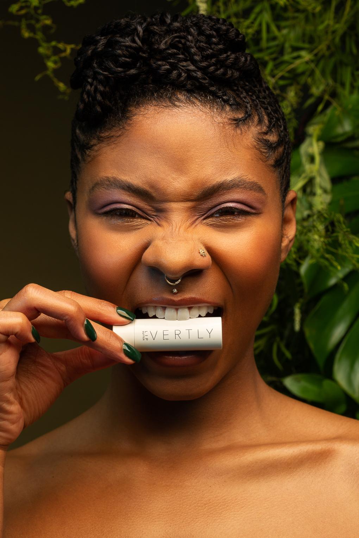 Beauty advertising portrait of black woman biting lipstick by women's photographer Ella Sophie