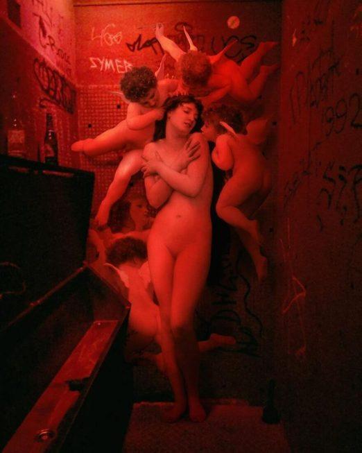 Pintura clásica de una mujer con ángeles en un cuarto de baño de un bar