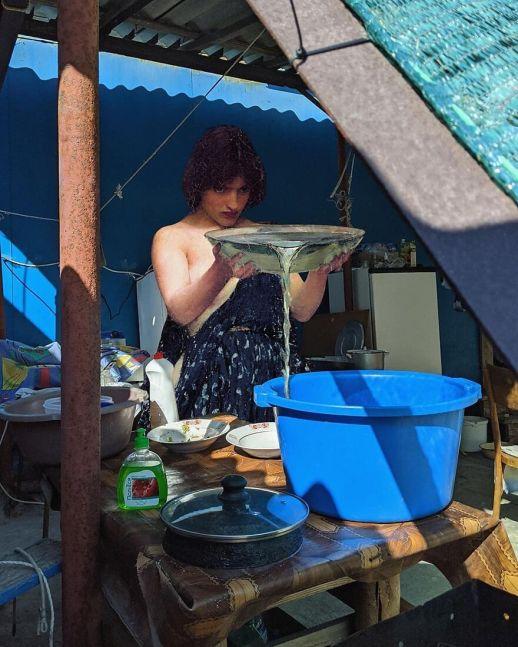 Mujer morena con un balde vertiendo agua en un cubo
