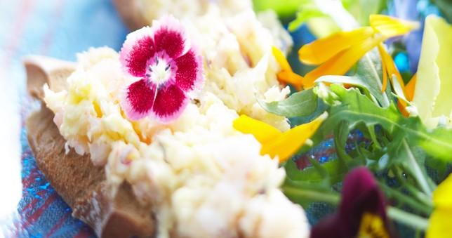 Ταρτάκια και σαλάτα  300 γραμμ. γαρίδες βρασμένες και καθαρισμένες  2 χούφτες λουλούδια (γαρίφαλα, χρυσάνθεμα, πανσέδες, τριαντάφυλλα κ.ά.)  75 γραμμ. ημιαλατισμένο μαλακό βούτυρο  2 φρέσκα κρεμμυδάκια  2-3 ματσάκια ρόκα  1 μπαγκέτα ψωμί  3 κ.σ. ελαιόλαδο  1 κ.σ. χυμό λεμονιού  αλάτι