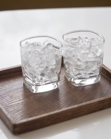 Glass of Ice on Wood Tray on Table Coffee Shop