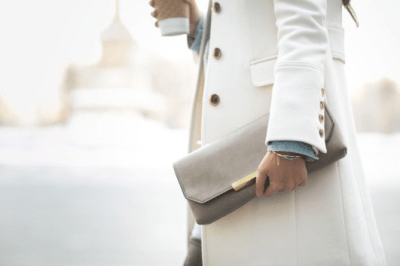 woman with winter white coat and clutch bag