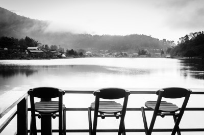 Three bamboo chairs on a village mountain lake