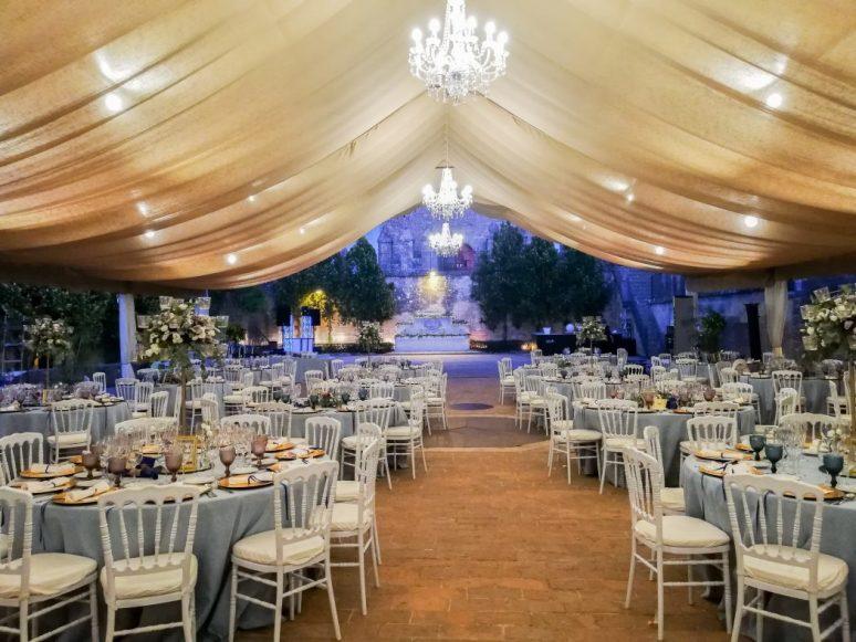 Salón de boda, una wedding planner te ayudará en la composición de la cena, su decoración e iluminación. Carcasa de mesas redondas con pasillo central. Combinado con lámparas chandelier y composición de centros altos y bajos con mantelería azul cielo.