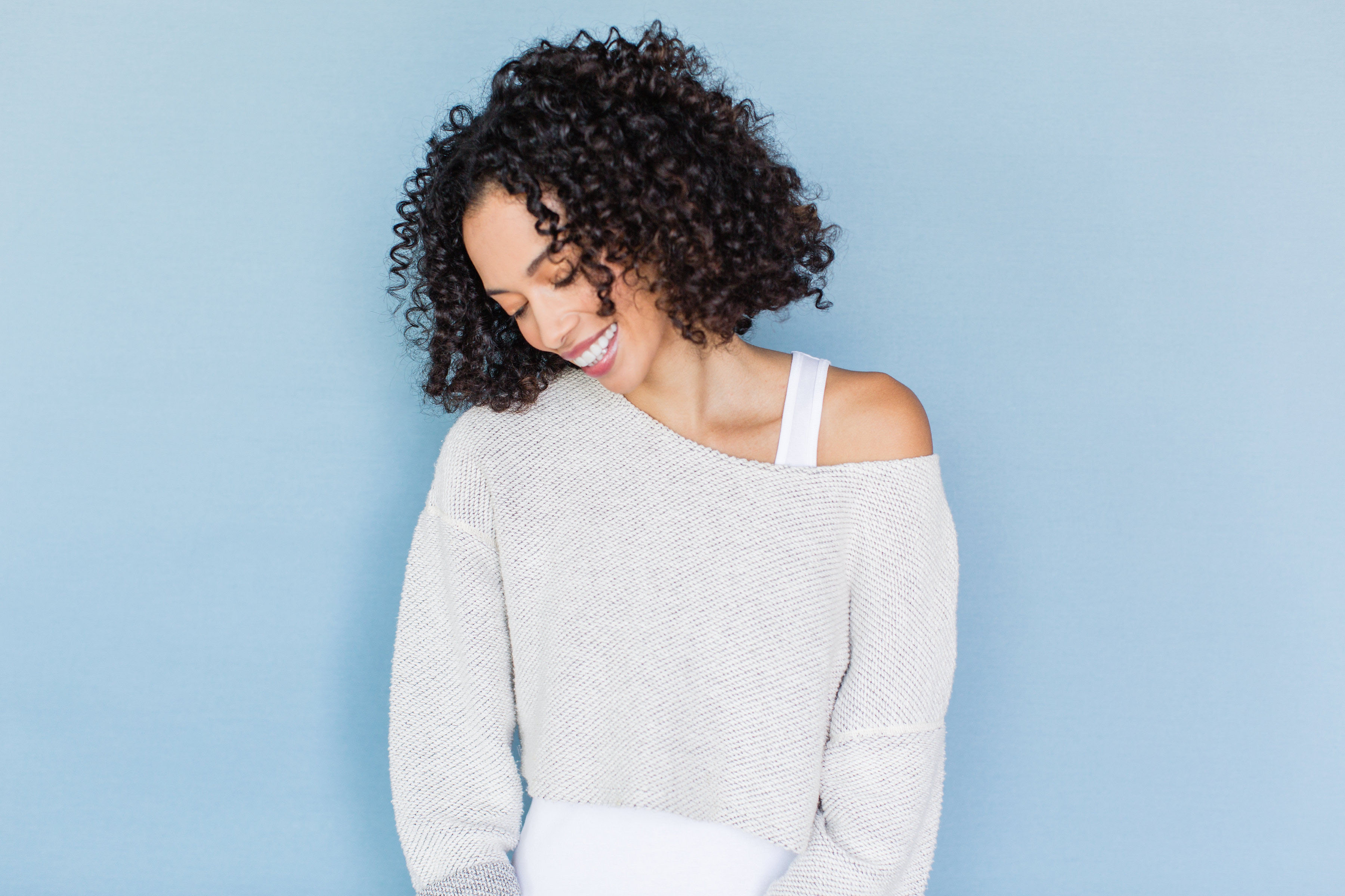 woman smiling in front of blue background