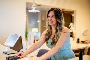 lauren siso atlanta esthetician at front desk smiling with skincare