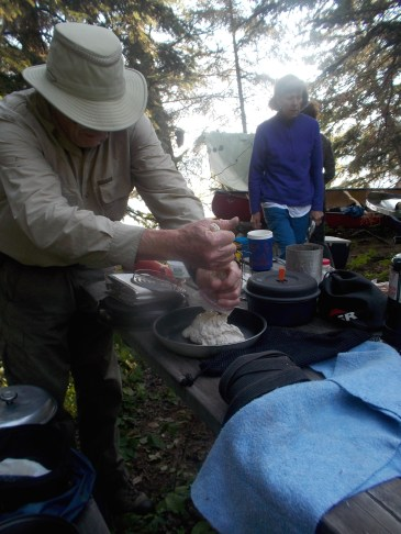Squeezing out the dough for bannock for breakfast