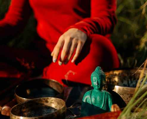 person in red long sleeve shirt holding green ceramic bowl