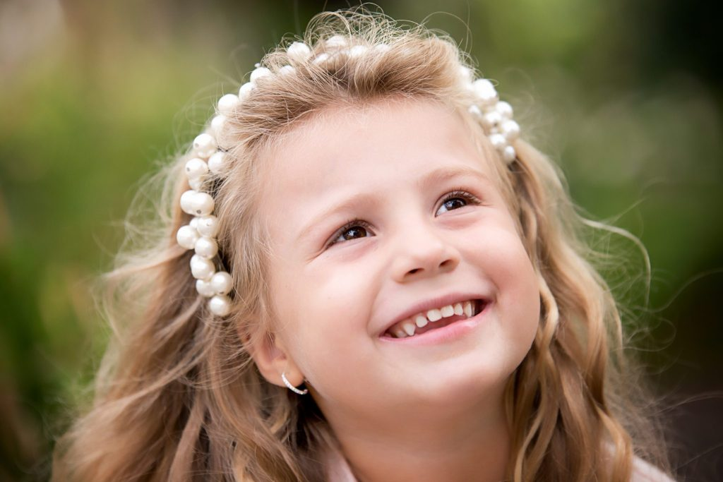 Little girl smiles up at her mom