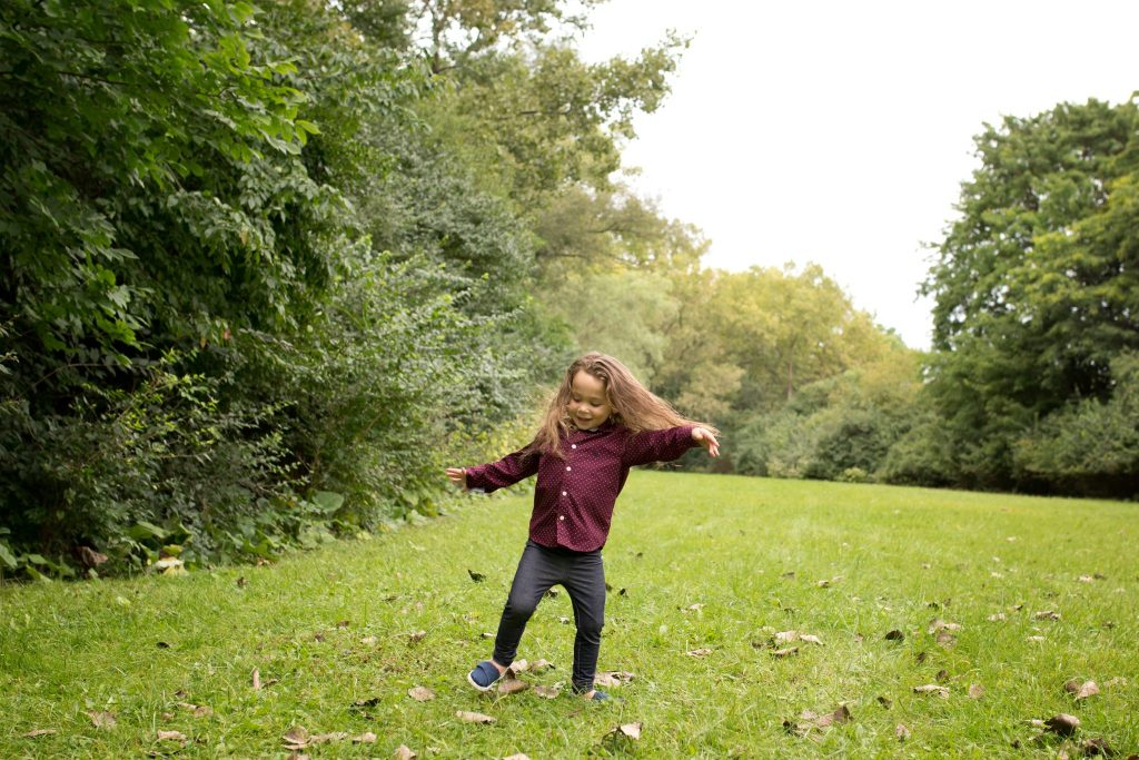 three year old boy with long brown hair playing in an open grassy area