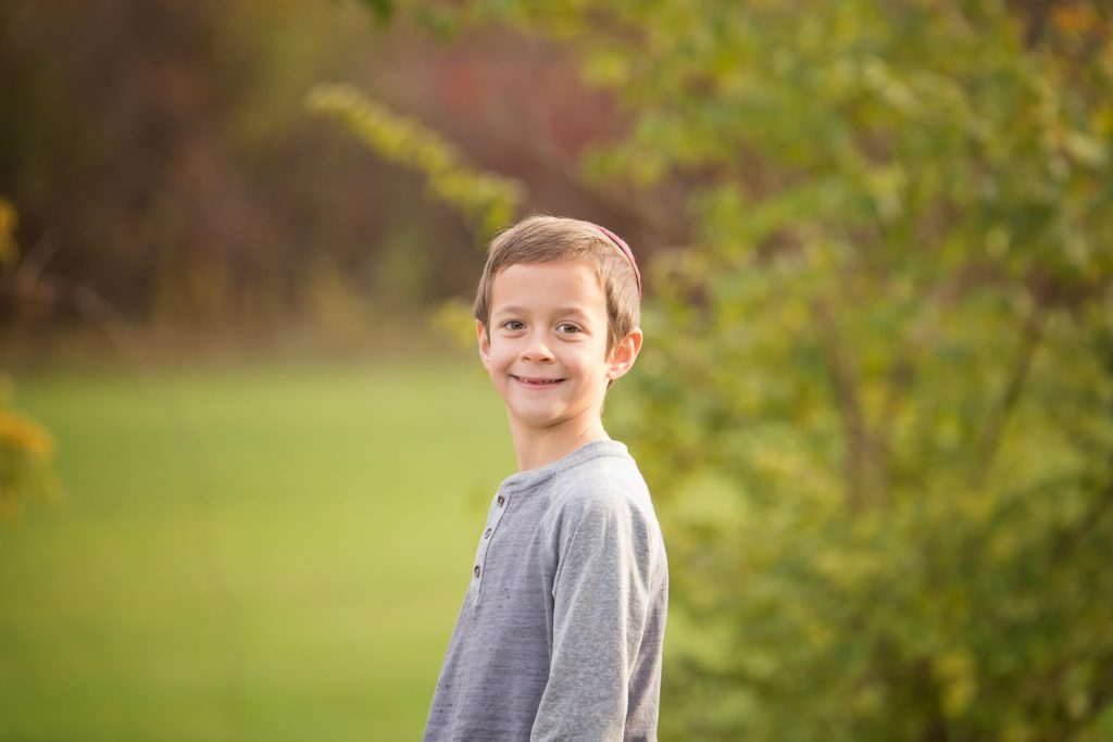 six year old boy poses in park in Beachwood with greenery behind him