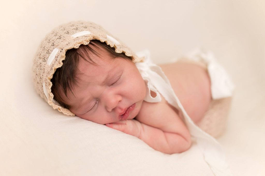 newborn baby girl on cream backdrop in bonnet
