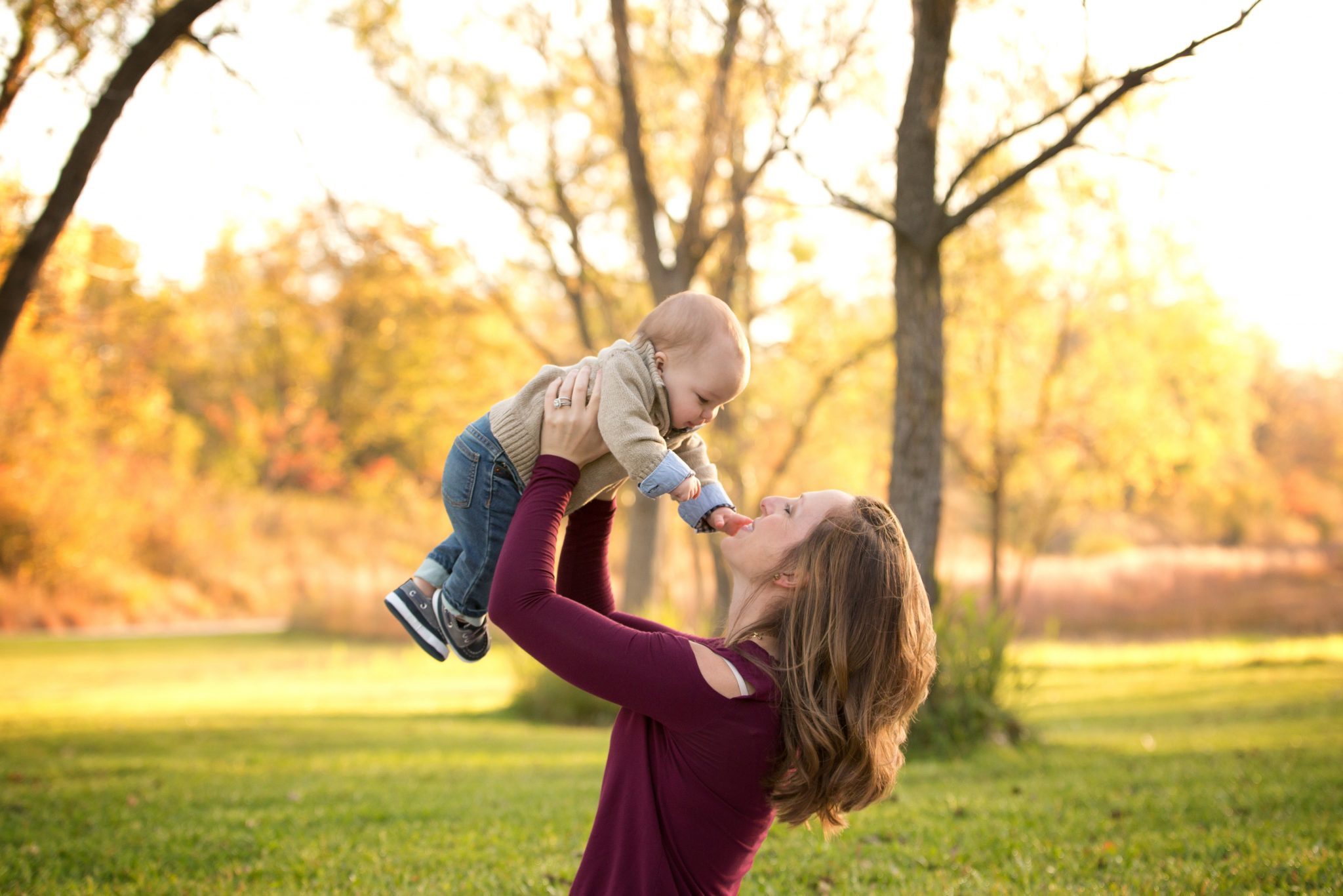 mom holding her baby boy up in the air with fall foliage behind them