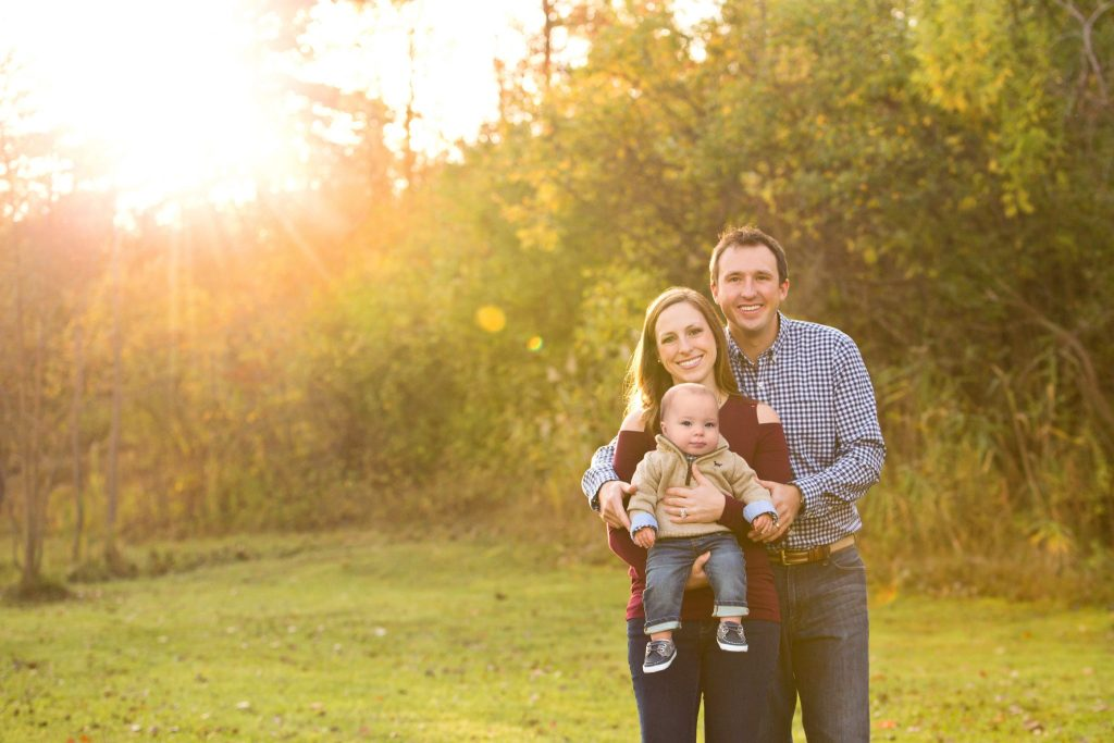family photo of parents and baby boy with fall foliage behind them and big sunburst