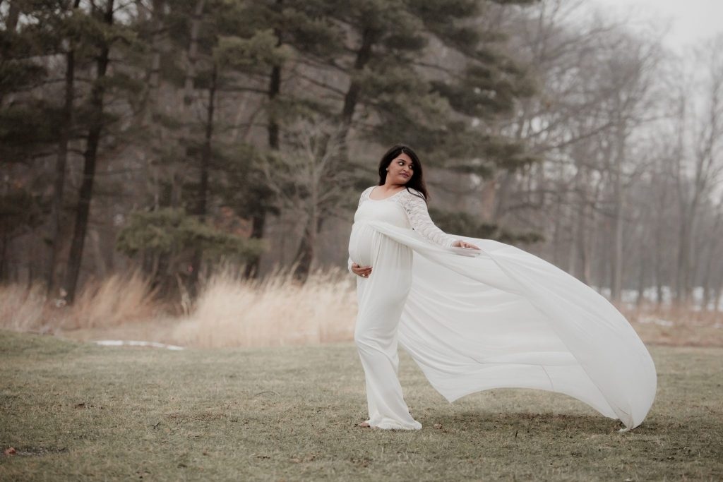 expectant mom holds her off-white maternity gown as it blows in the wind