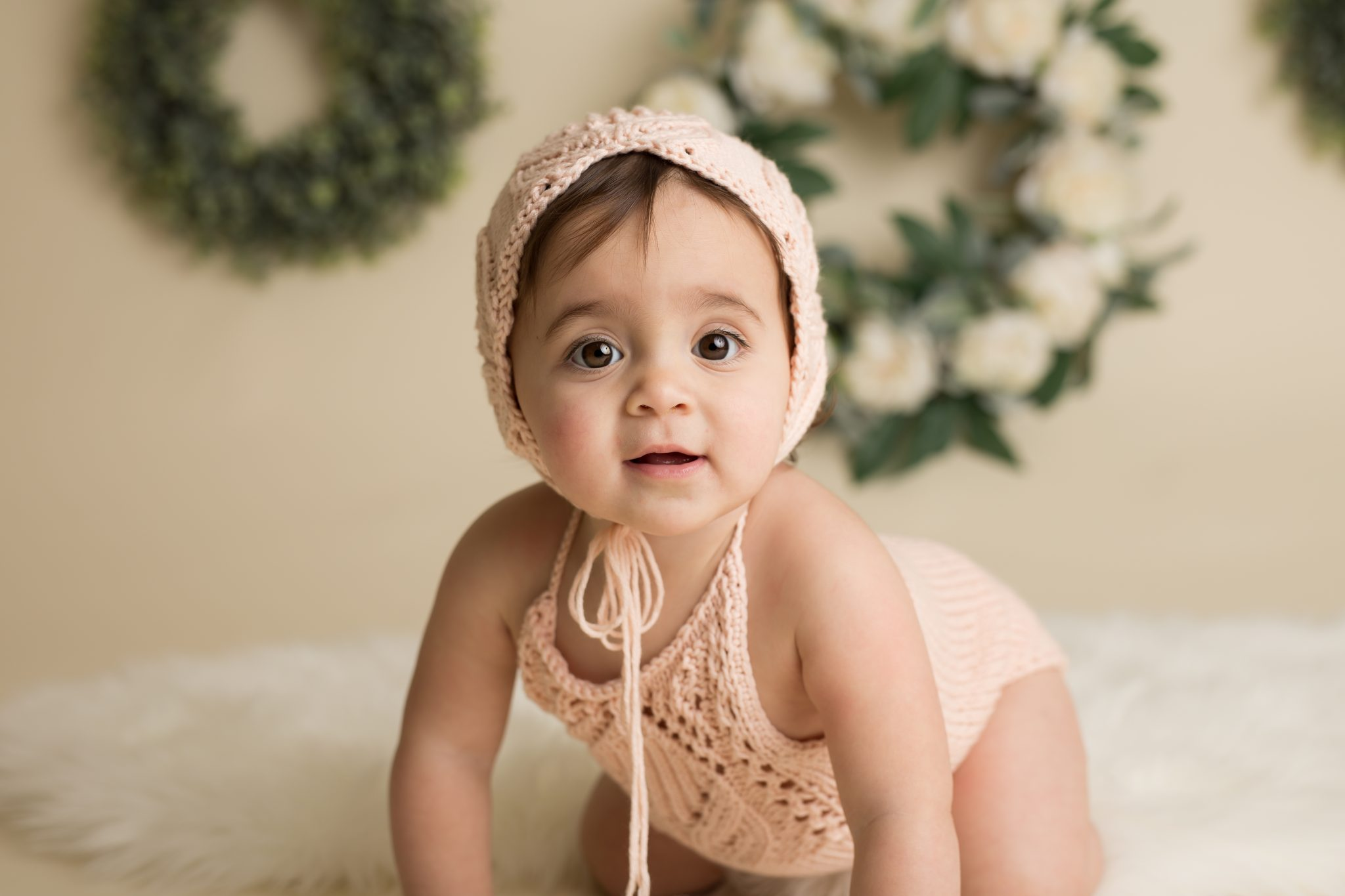 baby in peach bonnet and romper