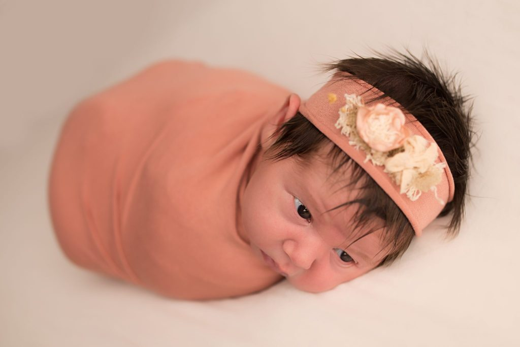 newborn baby girl in salmon color wrap and matching headband