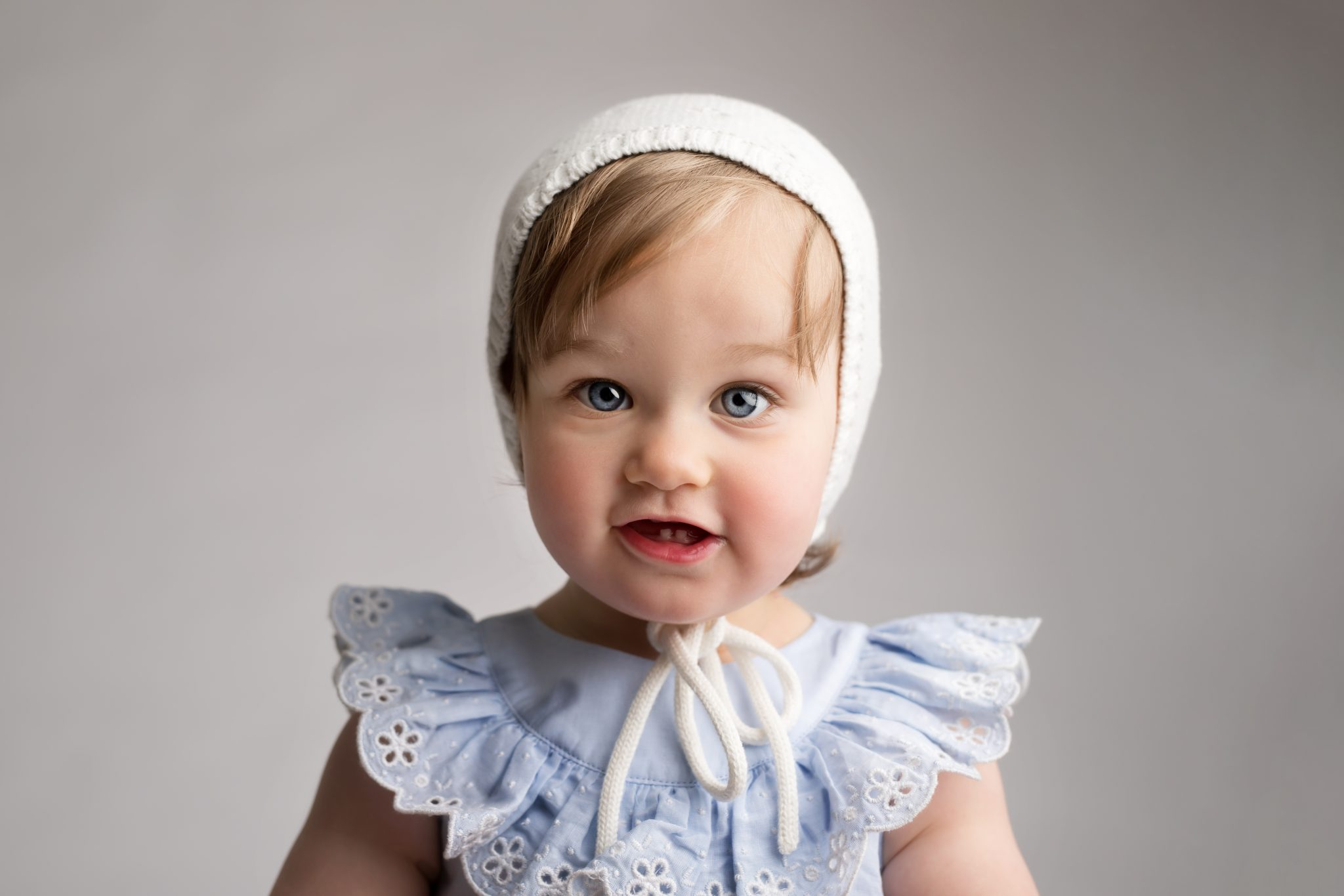 fifteen month old baby girl with blue eyes in white bonnet and blue dress