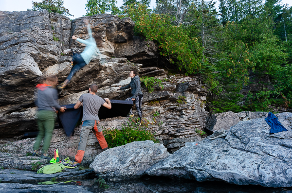 four people bouldering on the shore of lake huron