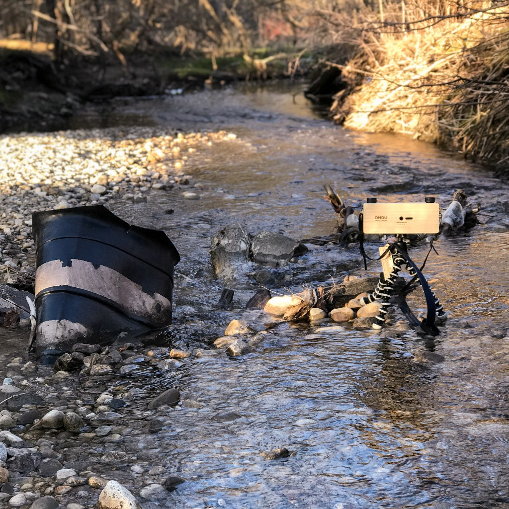 A picture of a pinhole camera taking a long exposure image of a shopping cart in a stream.
