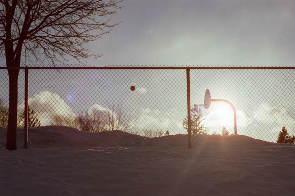 An image of a winter basketball game at sunset.