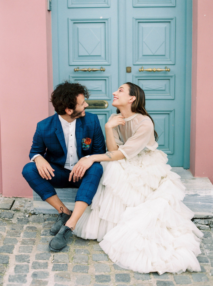 Bride and Groom informant of blue doors of a pink building in Athens