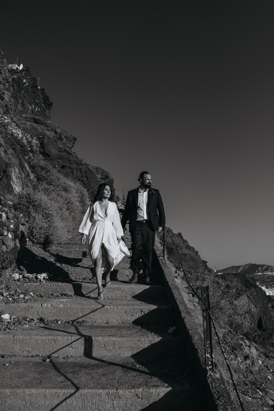 stylish Santorini elopement couple walking hand in hand in santorini