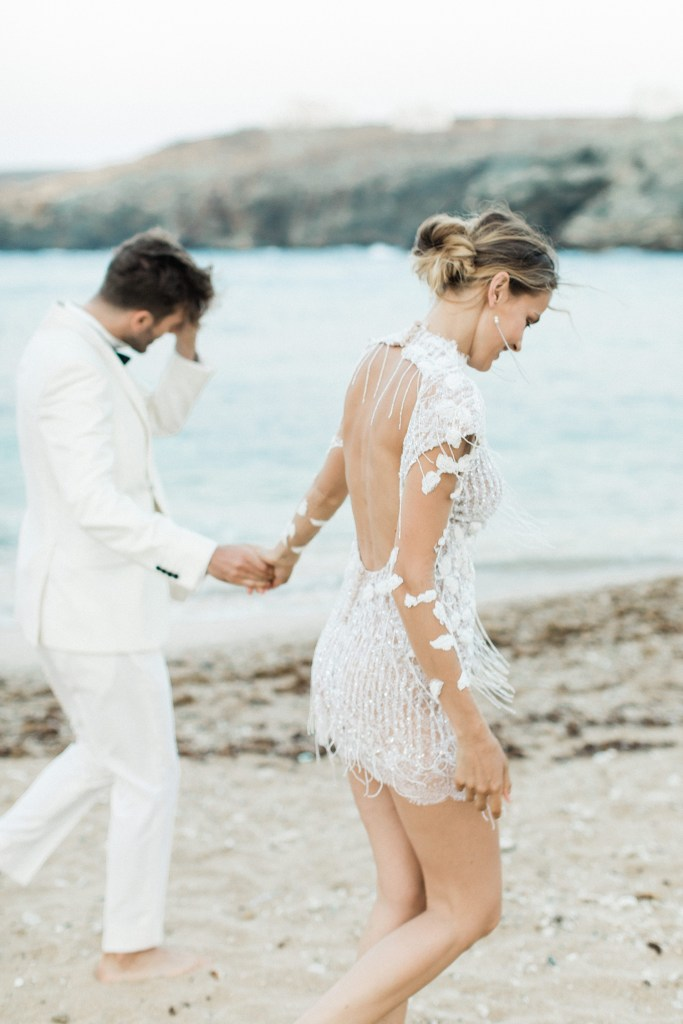 Bride in Mairi Maprola dress Love Story in Mykonos holding a grooms hand