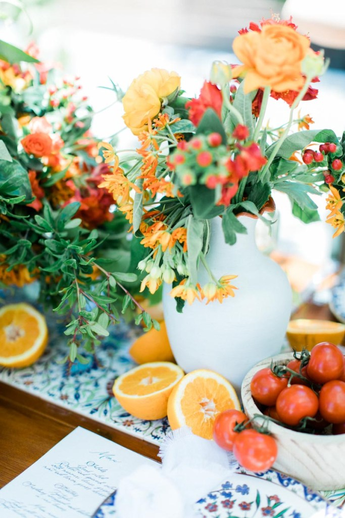 Greek food table setup with oranges and tomatoes