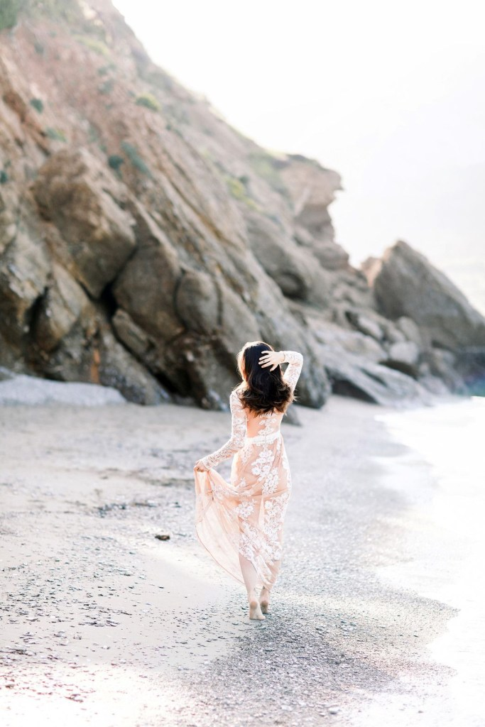 Bride walking on the beach at sunset