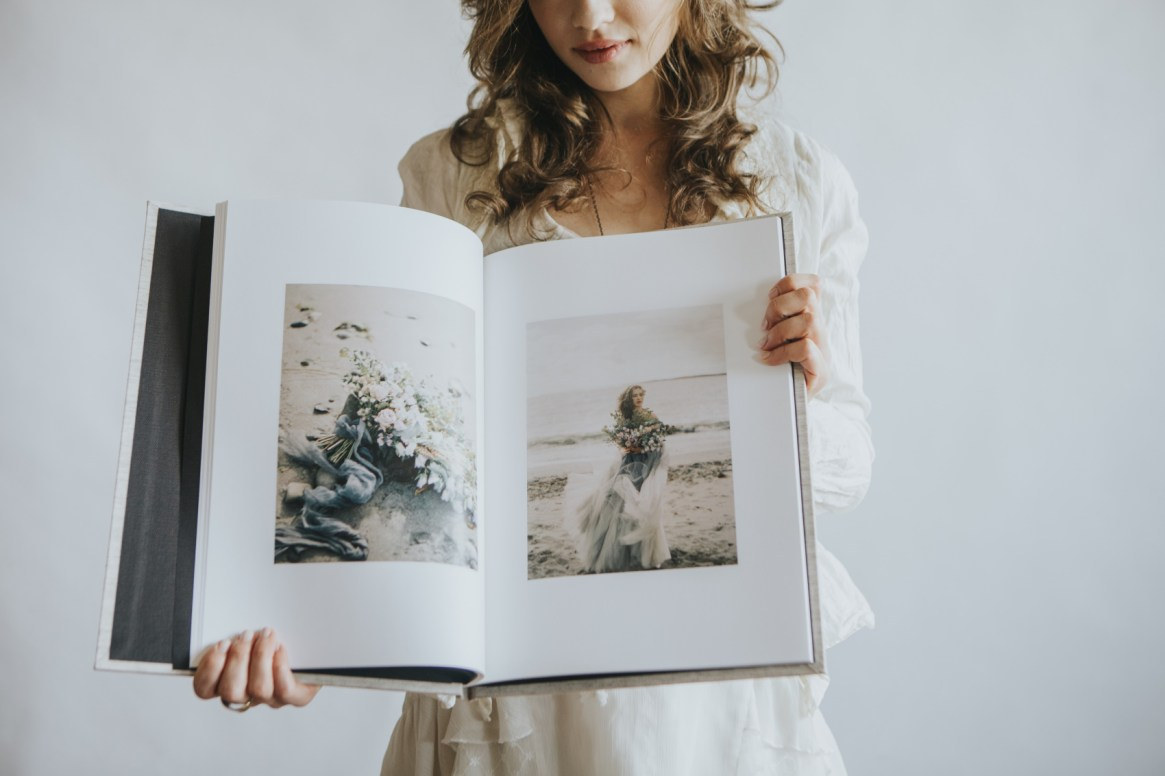 woman holding a wedding qt album heirloom edition