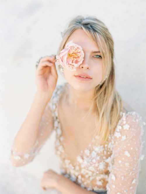 bride holding a rose on her eye