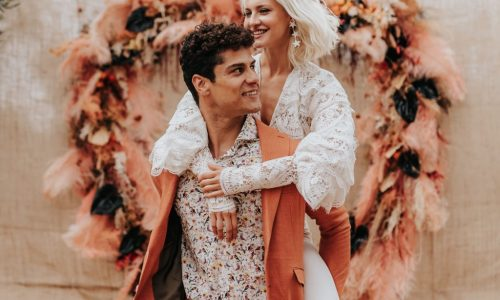 Bohemian heart-shaped backdrop in Athens with happy groom holding the bride on his back - piggybacking