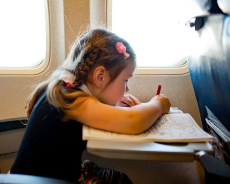 little girl coloring on airplane