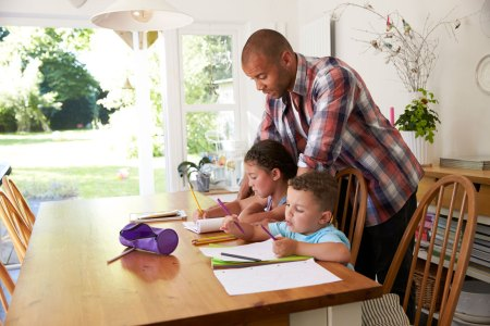 father helping children with homework