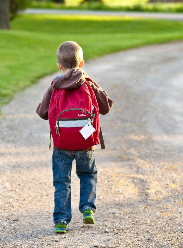 boy in brown hoodie carrying red backpack while walking